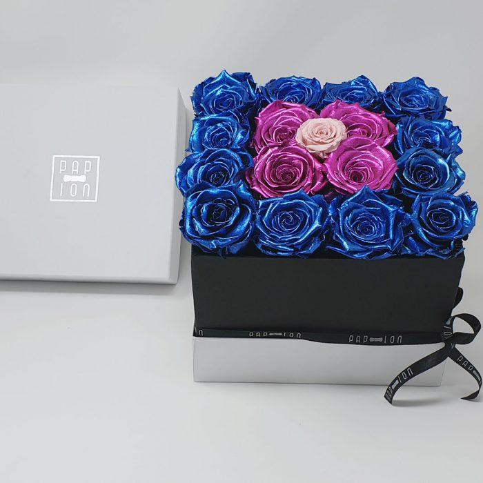 Cubo di rose rosa metalizzate circondato da rose blu metalizzate e punto luce rosa