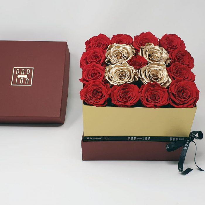 Cubo di rose dorate circondato da rose rosse e punto luce rossa